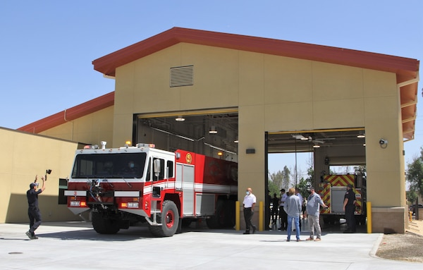 Leaders, firefighters, project engineers and contractors explore the newly constructed fire station at March Air Reserve Base in Riverside County, California, after its official unveiling May 6, 2021, while a firefighter directs a flight-line crash truck into one of the facility's two drive-through bays. The project was managed by the U.S. Army Corps of Engineers Los Angeles District.