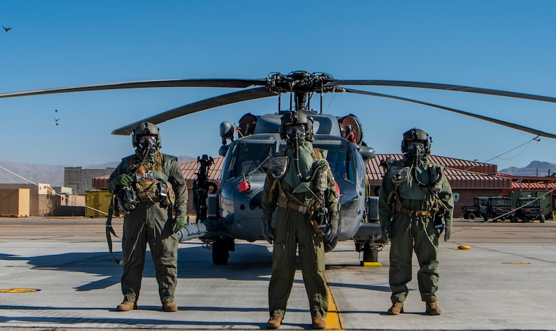 Airmen pose for photo in front of a helicopter.
