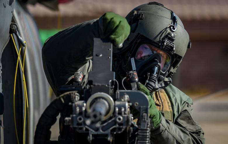 Airman performs pre-flight checks on aircraft.