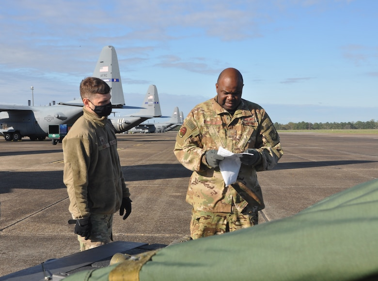 service members prepare to load cargo on an aircraft