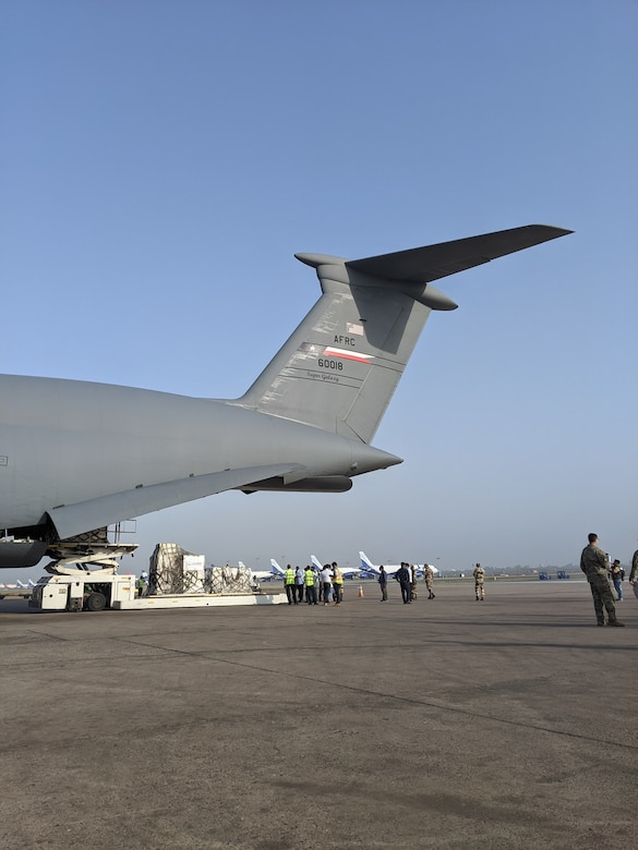 Ground crews offload COVID-19 medical treatment supplies from a 433rd Airlift Wing C-5M Super Galaxy May 4, 2021 at the airport in New Delhi, India. Multiple U.S. Air Force aircraft moved the supplies from Travis Air Force Base, California. (Courtesy photo)