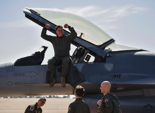 man sitting on a jet flexing his muscles