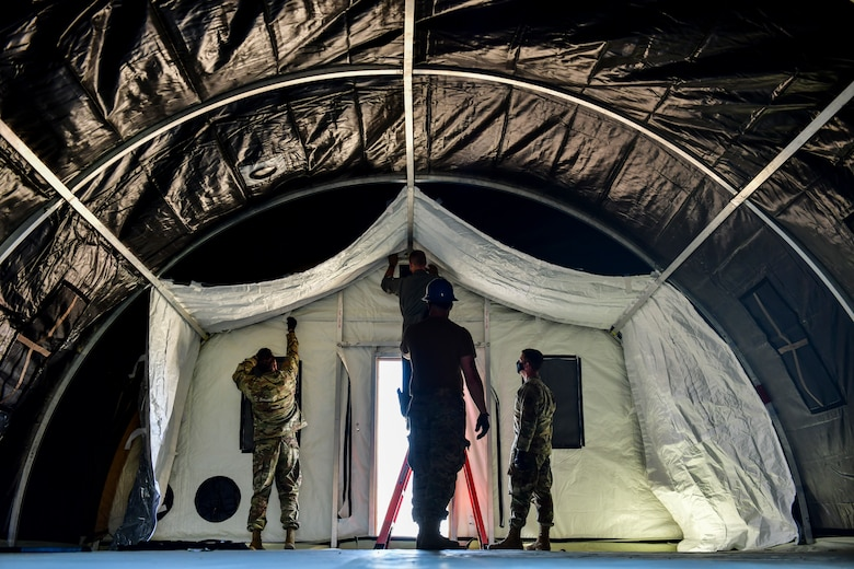Airmen set up a military shelter system