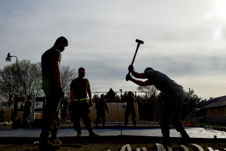 Airmen assigned to the 19th Airlift Wing stake down a military shelter system