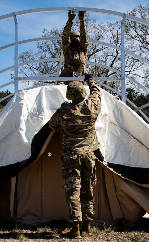 Airmen assemble a military shelter system