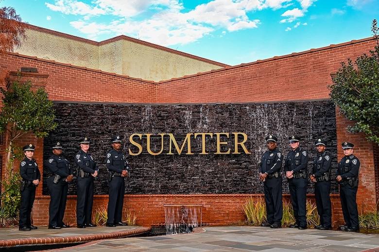 A photo of police officers standing in front of a sign