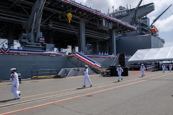 The crew of USS Miguel Keith (ESB 5) prepare to board the ship during the ship's commissioning ceremony.