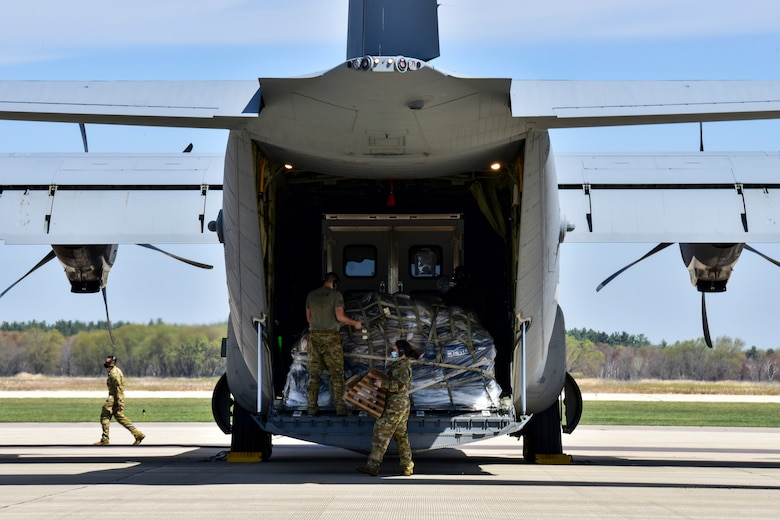 Airmen assigned to the 61st Airlift Squadron prepare to offload cargo from a C-130J Super Hercules
