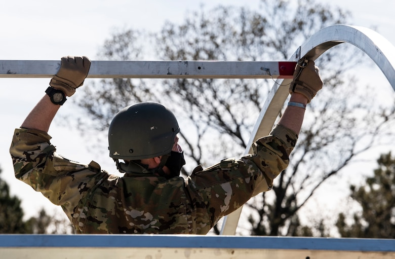 An Airman assigned to the 19th Airlift Wing assembles a military shelter system