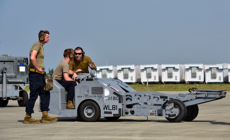 """A weapons load crew load operate a MJ-1 Bomb Lifter """"Jammers"""""""