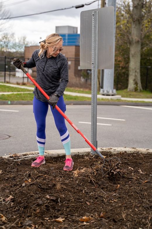 210417-N-EJ843-0005 GROTON, Conn. (April 17, 2021) Sarah Simons removes old soil before planting new plants outside of Naval Submarine Base (SUBASE) New London. The Simons' started a beautification project on base after seeing trash and the need for improvement in certain areas. With a love for finding ways to make the community look better, the Simons' noticed the outside of the base didn't have many flowers or shrubs. After talking to SUBASE Public Works, the Town of Groton, and the state Department of Transportation they received approval for their beautification project near the base's Main Gate. (U.S. Navy photo by Mass Communications Specialist Seaman Jimmy Ivy III/Released)