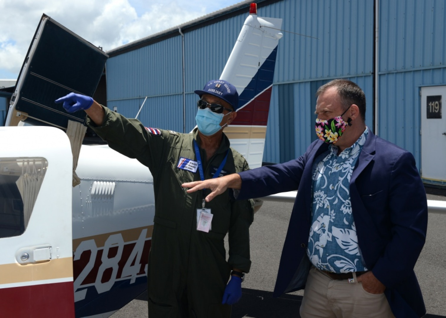 Coast Guard Auxiliarist Bob Emami and Lt. Gov. Josh Green of Hawaii load masks aboard a Coast Guard Auxiliary airplane at Daniel K. Inouye International Airport, Hawaii, May 28, 2020. Two Coast Guard Auxiliary airplanes transported 60,000 masks to Maui as part of the state of Hawaii's COVID-19 pandemic response. (U.S. Coast Guard photo by Petty Officer 3rd Class Matthew West/Released)