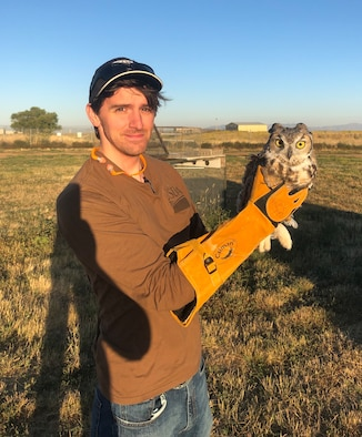 Tyler Adams, a US Department of Agriculture wildlife biologist at Hill AFB, displays an owl captured near the base's flight line. The bird will be taken to a new habitat as part of the Raptor Relocation Program, which focuses on trapping kestrels, hawks, owls, and other raptors and relocating the birds to safer and more suitable habitats away from the airfield.
