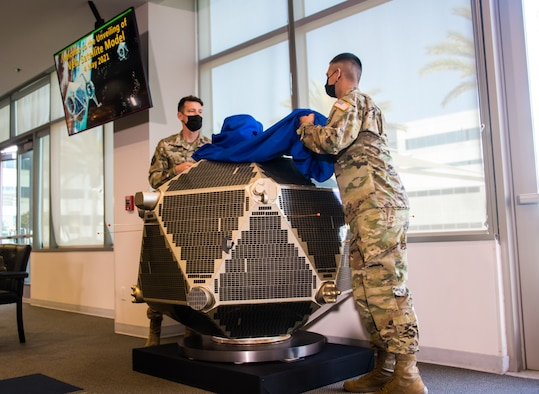 Two Guardians reveal a full-scale Vela satellite model, presented by representatives from Northrop Grumman to the U.S. Space Force's Space and Missile Systems Center at Los Angeles Air Force Base, California, May 4, 2021. Originated in 1960, Vela was the first space-based system used for nuclear surveillance. Today, the mission of monitoring nuclear detonations continues with payloads hosted on GPS satellites. (U.S. Space Force photo by Van Ha)