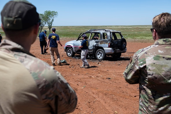 U.S. Air Force members watch as FBI special agents demonstrate how they would grid an area for a post-blast investigation.