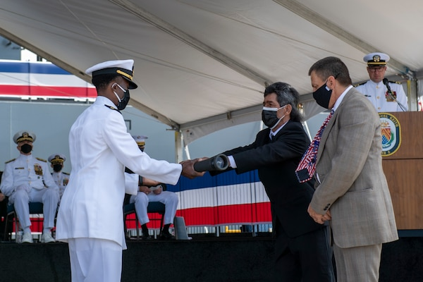 Jesse Mendez presents Lt. Justin Woods, the first officer of the deck of USS Miguel Keith (ESB 5), with a long glass during the ship's commissioning ceremony.