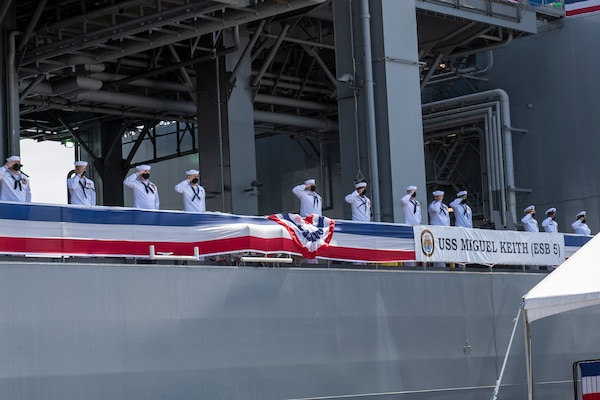 The crew of the Lewis B. Puller-class expeditionary mobile base USS Miguel Keith (ESB 5) salute guests during the ship's commissioning ceremony.