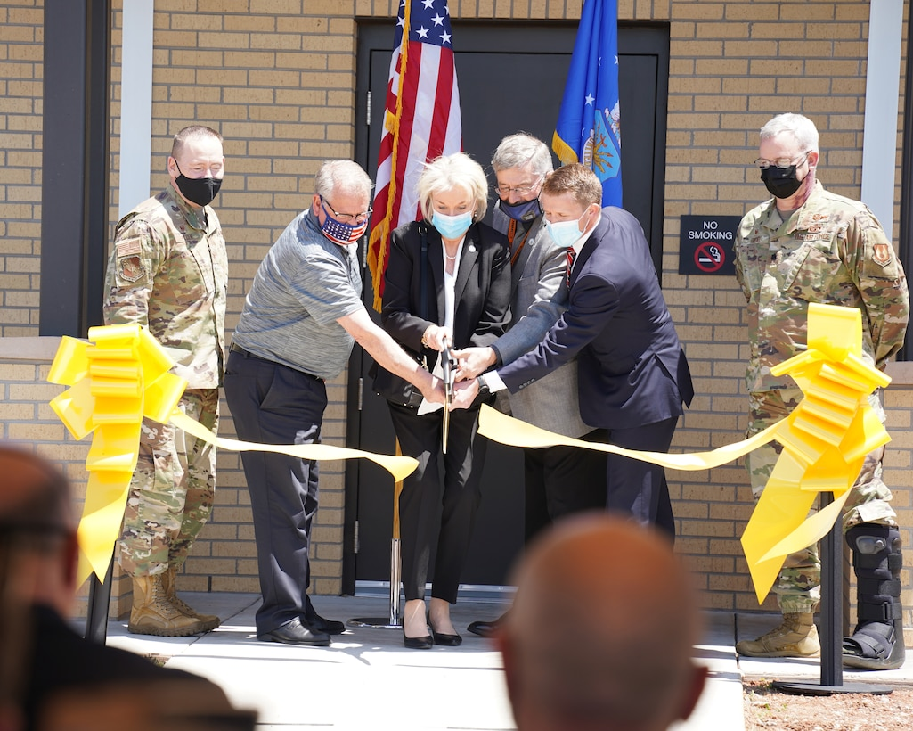 A group of people cutting a ribbon