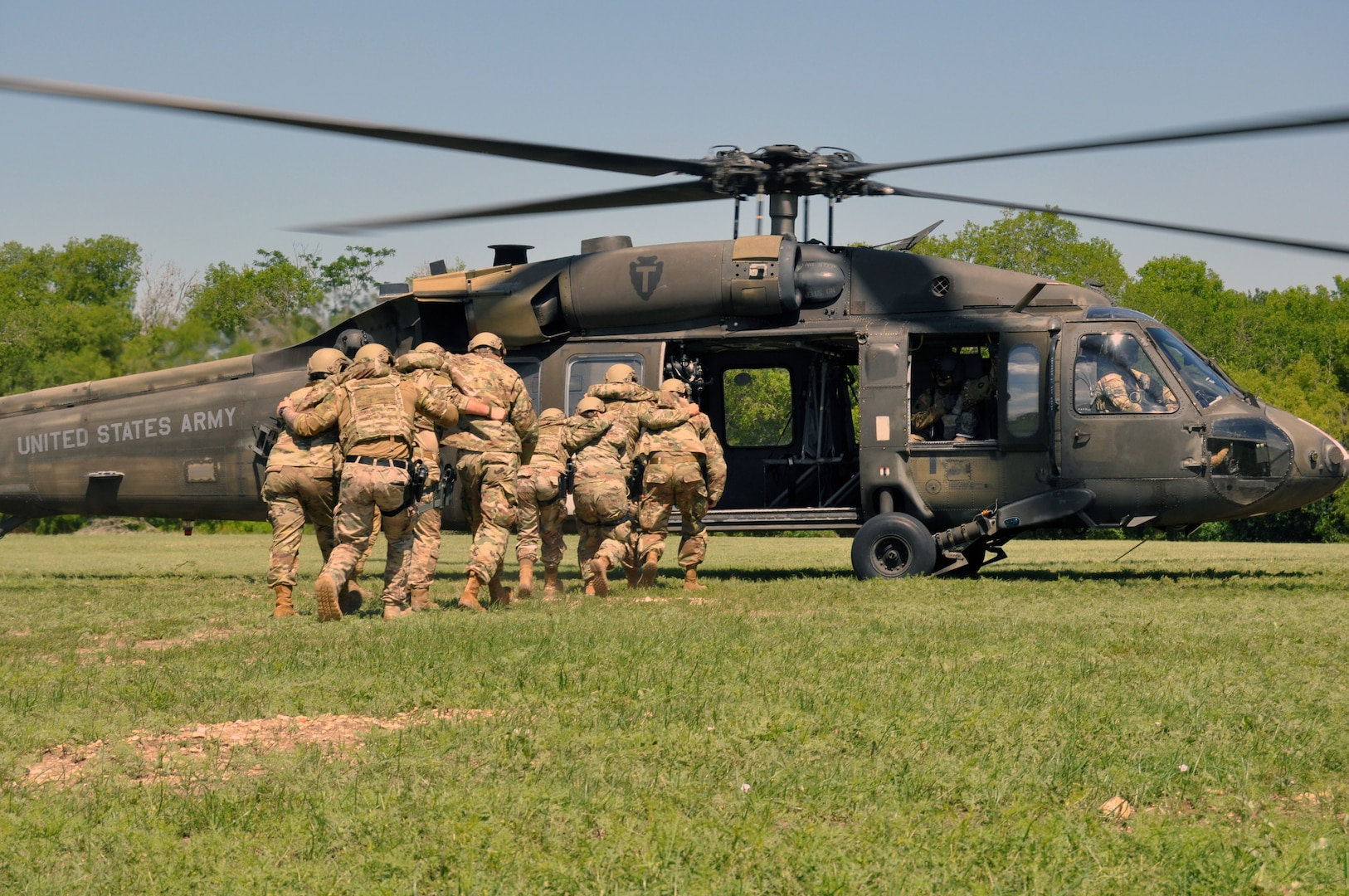 Airmen load simulated injured Airmen onto helicopter.