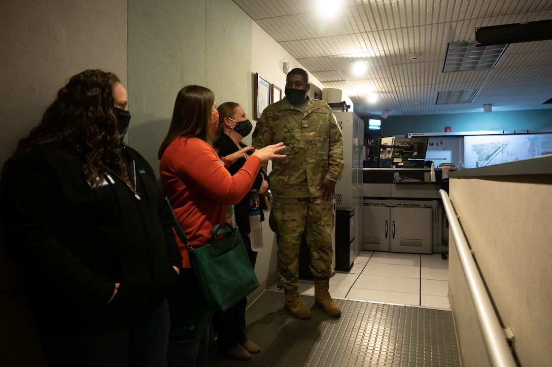 Senior Airman Sterling Tate, right, 341st Civil Engineer Squadron firefighter, escorts military spouses into the Base Defense Operations Center during a tour May 7, 2021, at Malmstrom Air Force Base, Mont.