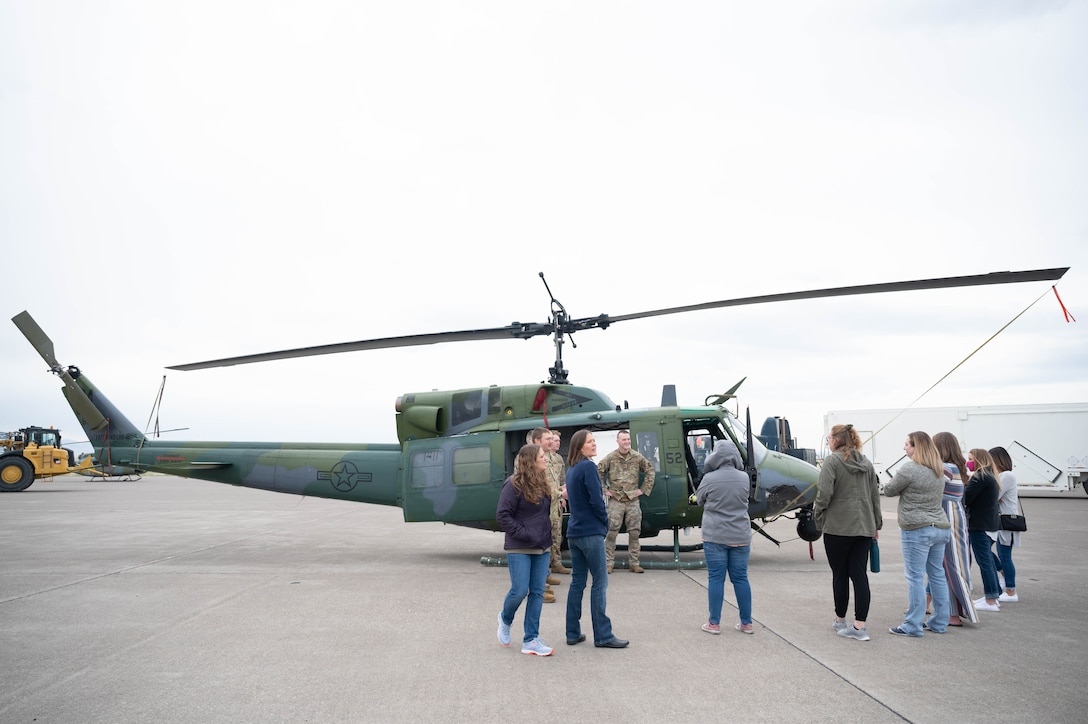 """Members of the 40th Helicopter Squadron explain their mission to military spouses and show off a UH-1N """"Huey"""" helicopter during a tour May 7, 2021, at Malmstrom Air Force Base, Mont."""