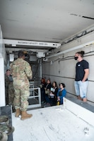Maintainers from the 341st Missile Maintenance Squadron explain their mission to military spouses inside a weapon transport vehicle during a tour May 7, 2021, at Malmstrom Air Force Base, Mont.