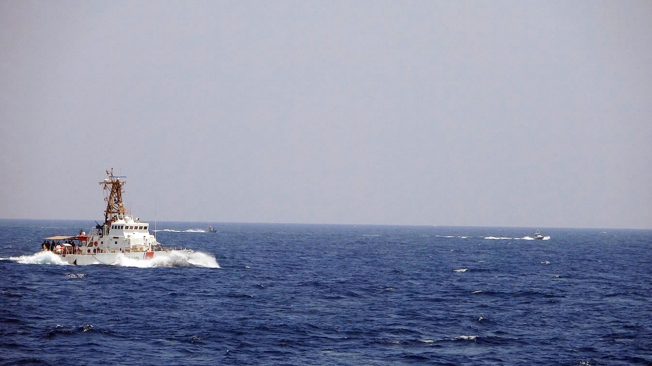 A Coast Guard vessel moves through blue ocean waters. In the rear, two smaller speed boats maneuver in the water.