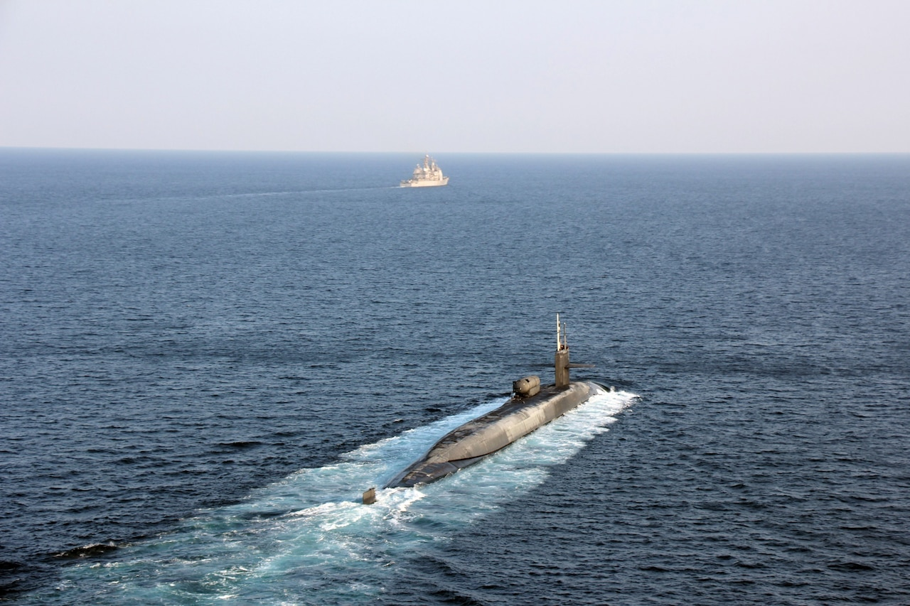 A submarine moves through the water. Far in front of it is a surface vessel.