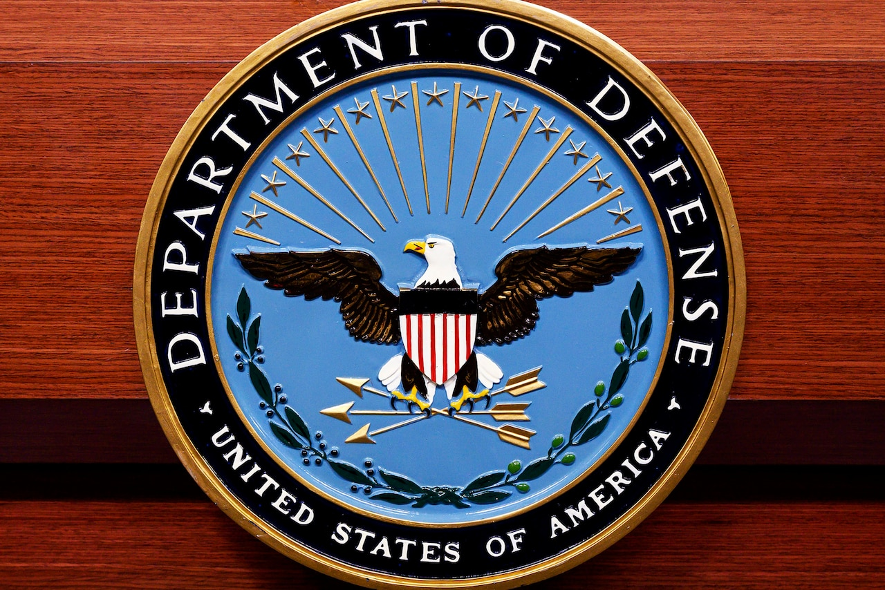 The Defense Department seal adorns a wooden lectern.