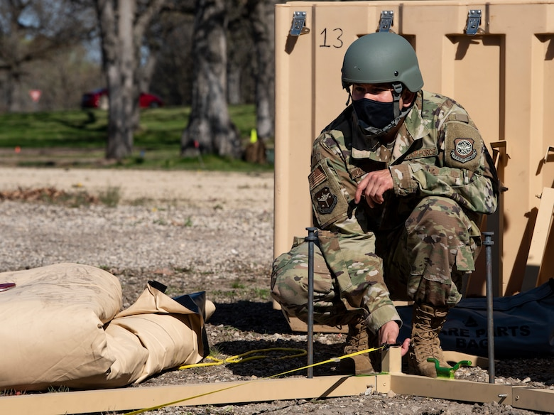 An Airman assembles a military shelter system