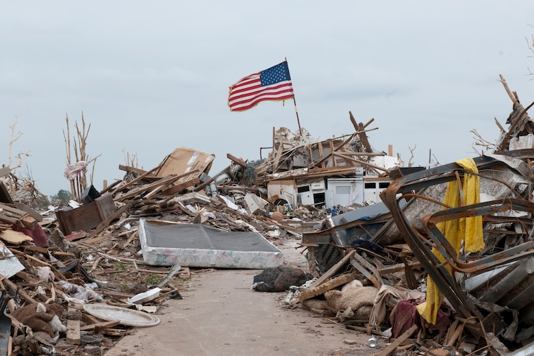 The U.S. flag standing atop mounds of debris where homes were destroyed by a tornado.