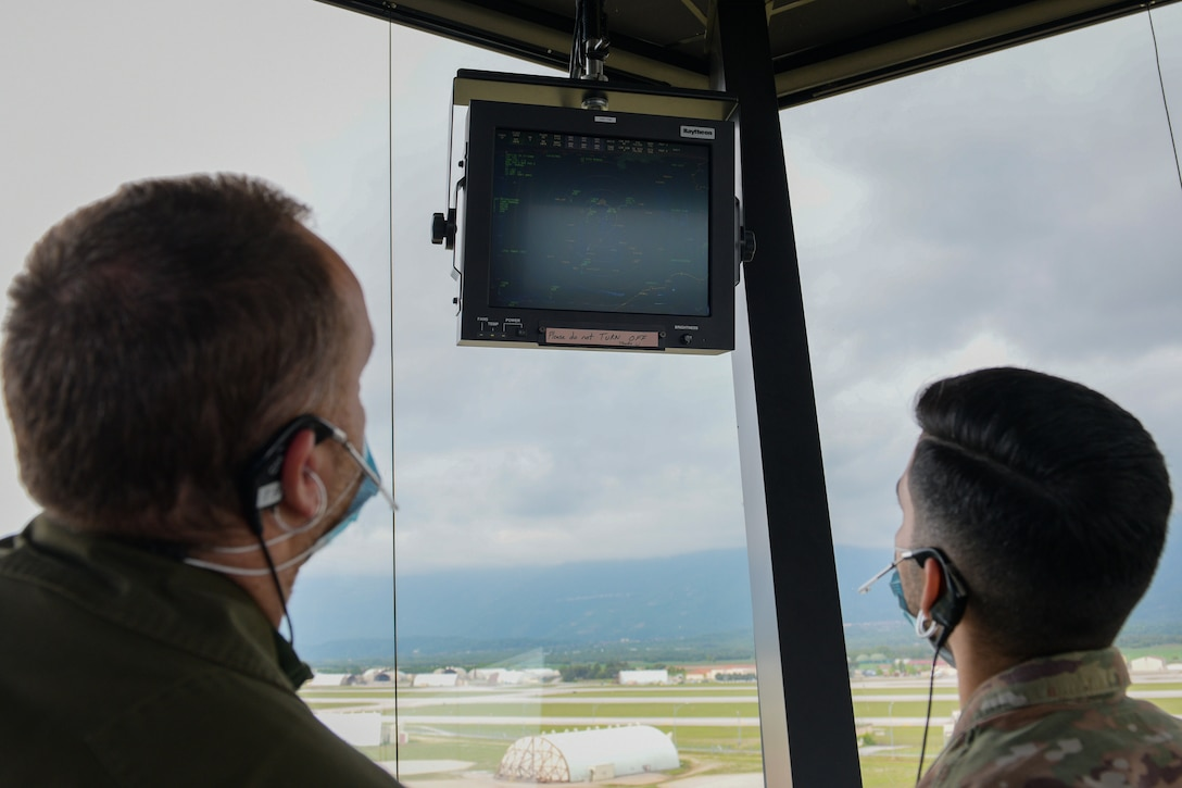 Italian air force Maresciallo Francesco Di Maggio, Air Traffic Control Service, air traffic controller (ATC), left, and U.S. Air Force Staff Sgt. Daniel Cabezas, 31st Operations Support Squadron ATC, review flight data in the Air Traffic Control Tower at Aviano Air Base, Italy, May 7, 2021. ATCs plot aircraft positions on radar equipment and compute aircraft speed, direction and altitude. The U.S. Air Force and ITAF ATCs work together to relay flight and landing instructions, weather updates, and safety information to the pilots. (U.S. Air Force photo by Airman 1st Class Brooke Moeder)
