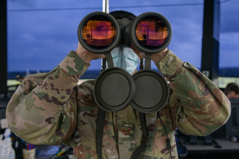 U.S. Air Force Staff Sgt. Daniel Cabezas, 31st Operations Support Squadron (OSS) air traffic controller, scans the horizon for landing lights and obstructions on the flight line at Aviano Air Base, Italy, May 7, 2021. The ATCs observe aircraft in their airspace and monitor different variables such as wind speed and altitude. The 31st OSS provides current operations planning, air traffic control, airfield management and weather and intelligence support. (U.S. Air Force photo by Airman 1st Class Brooke Moeder)