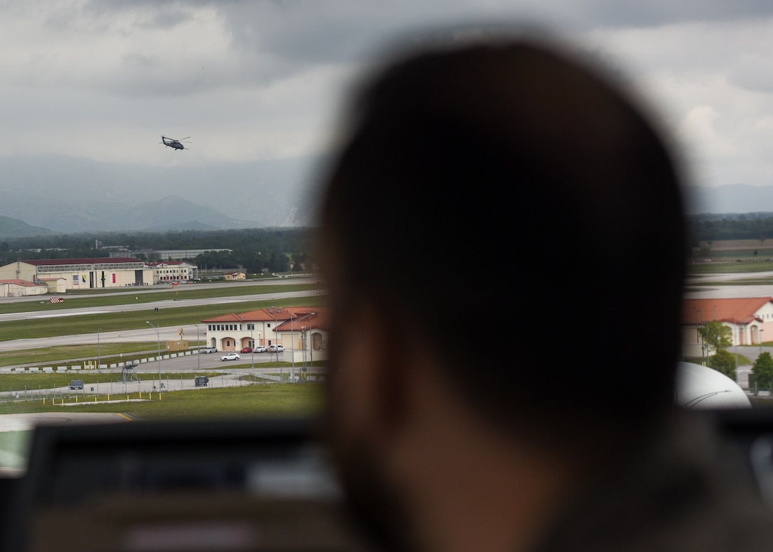 Italian air force Maresciallo Gianluca Farina, Air Traffic Control Service, air traffic controller (ATC), watches an HH-60 Pave Hawk takeoff from the Air Traffic Control Tower at Aviano Air Base, Italy, May 7, 2021. ATCs plot aircraft positions on radar equipment and compute aircraft speed, direction and altitude. ATCs ensure the safety of the pilots, aircraft and civilians on the ground by staying vigilant and spotting complications before they happen. (U.S. Air Force photo by Airman 1st Class Brooke Moeder)