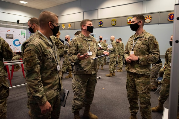 U.S. Air Force Col. Kurt Wendt, center, 501st Combat Support Wing commander, and Chief Master Sgt. Daniel Keene, left, 501st CSW command chief, learn about the innovation idea of Staff Sgt. Derek Ricks, right, 423rd Security Forces Squadron noncommissioned officer in charge of police services, at the Pathfinder Innovation Conference 2021 at Royal Air Force Croughton, England, May 6, 2021. The 501st CSW hosted its first innovation conference to highlight new ideas and promote a culture of innovation within the wing. (U.S. Air Force photo by Senior Airman Jennifer Zima)