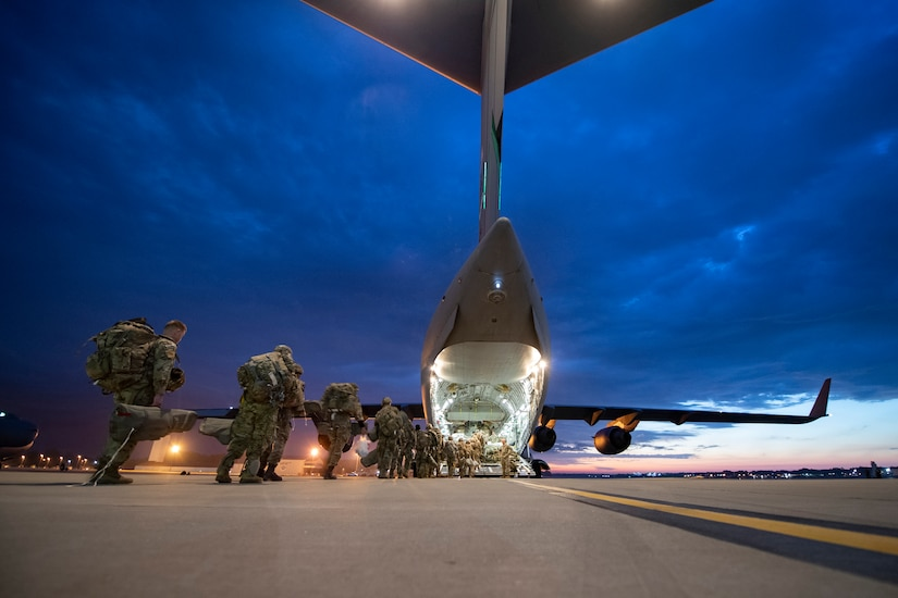 A line of soldiers board a large military aircraft under a dark sky.