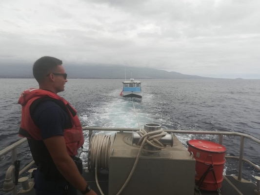 Coast Guard Enlisted Person of the Year, Seaman Theodore Kirkbride, aids in the towing of a vessel in Maui. Kirkbride has assisted in over 15 search and rescue cases, saving over 22 lives. (U.S. Coast Guard courtesy asset)