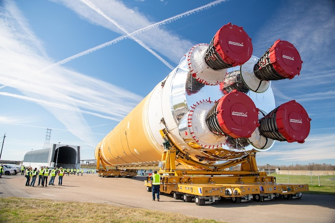 A large rocket, several meters tall, is transported on its side to a large hanger facility.