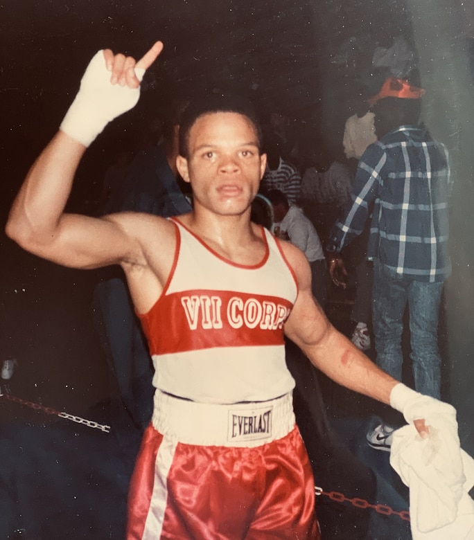 A young, male boxer poses for a photo.