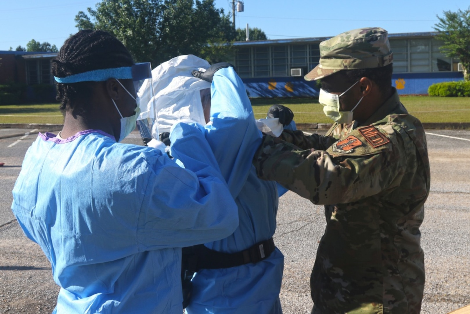 Airmen assigned to the 186th Air Refueling Wing, Mississippi Air National Guard, help U.S. Air Force Tech. Sgt. Adriana Campbell-Page, COVID-19 test administrator, put on her personal protection equipment at a mobile testing site in De Kalb, Miss., Apr. 24, 2020. The DLA Troop Support Medical PPE team earned Team of the Year Award for their 2020 COVID-19 support, and DLA Troop Support employees Linnette De La Cruz and John Trunzo also earned Employee and Supervisor of the Year Awards, respectively, for their 2020 mission support.
