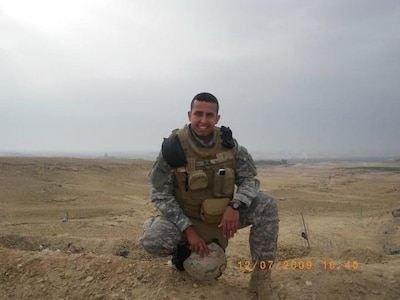 man in uniform wearing safety gear poses for a photo.