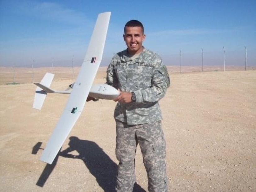 man standing holding a unmanned aircraft in his hand.