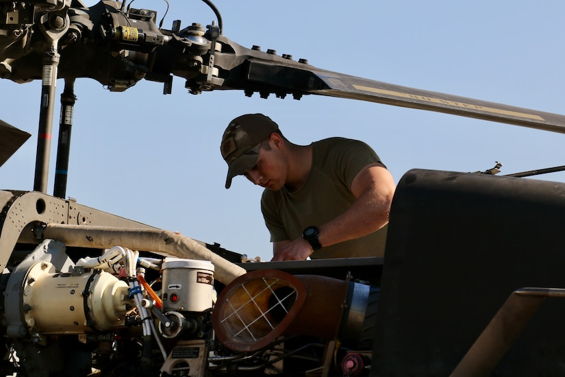 A man works on a helicopter.