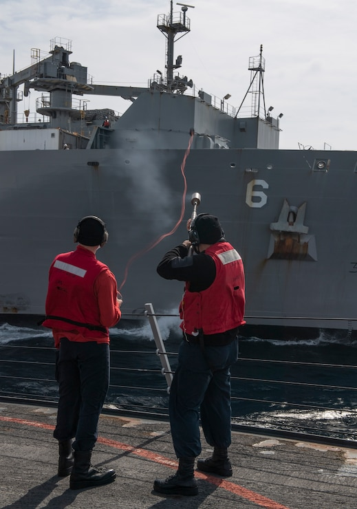 Sailors aboard USS Rafael Peralta (DDG 115) fire a shot line to the Lewis and Clark-class dry cargo ship USNS Amelia Earhart (T-AKE-6) during a vertical replenishment (VERTREP).
