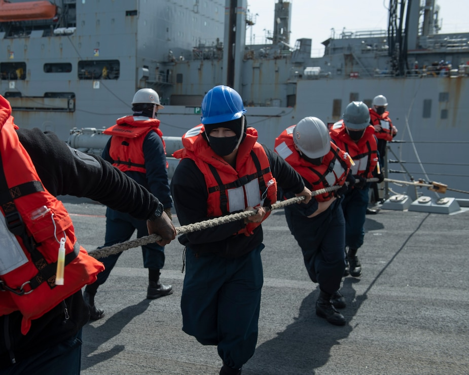 Sailors aboard destroyer USS Rafael Peralta (DDG 115) haul in the spanning wire from the USNS Amelia Earhart (T-AKE-6) during a vertical replenishment (VERTREP).