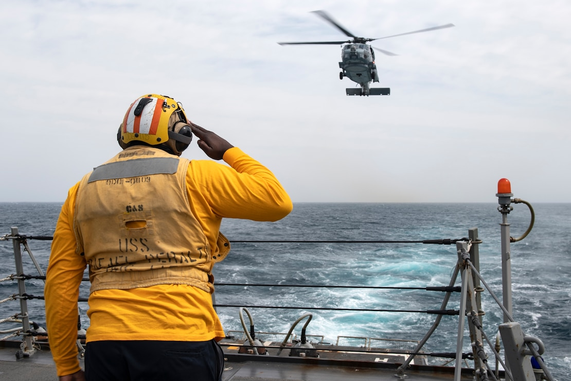 A Sailor salutes the pilot of an MH-60R Seahawk aboard USS Rafael Peralta (DDG 115) during a vertical replenishment (VERTREP) with USNS Amelia Earhart (T-AKE-6).