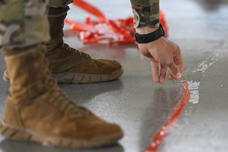 U.S. Air Force Airman Jorge Rosado, 42nd Medical Group Biomedical Equipment Apprentice, removes a line boundary at Maxwell Air Force Base, Alabama, May 7, 2021. The current COVID-19 vaccination site is moving from Maxwell's Honor Guard hanger to the Immunizations Clinic.