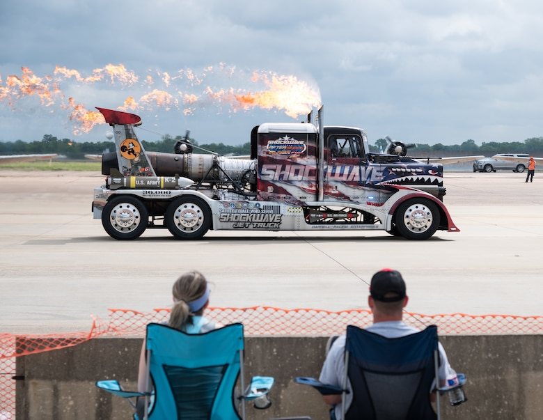 Spectators watch as the Shockwave Jet Truck performs a demonstration at the 2021 Defenders of Liberty Air & Space Show at Barksdale Air Force Base, Louisiana, May 9, 2021. The Barksdale Air Force Base Air & Space Show allows Shreveport-Bossier City to showcase the home of the B-52H Stratofortress, grant access to tour the military installation, view military and aerobatic performers, and support the recruiting arm of our armed forces. (U.S. Air Force photo by Airman 1st Class William Pugh)