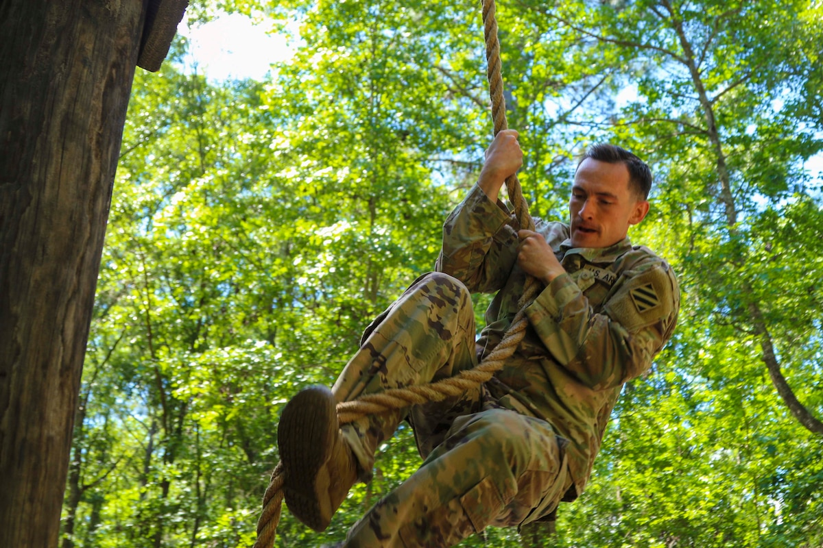 A soldier climbs a rope in a wooded area.