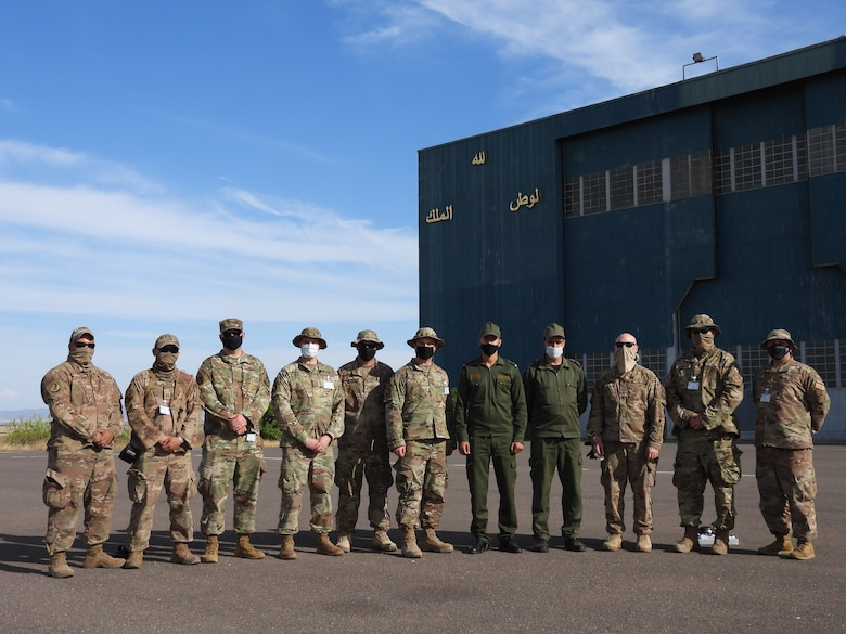 """Airmen with the 621st Contingency Response Wing airfield survey team and members of the Royal Moroccan Air Force pose for a group photo in front of an aircraft hangar at Ben Guerir Air Base, Morocco, April 21, 2021. The Royal Moroccan Air Force motto """"God, Country, King"""" can be seen written in Arabic on the hangar. Missions like this allow Devil Raiders to strengthen relationships with partner nations. (courtesy photo)"""